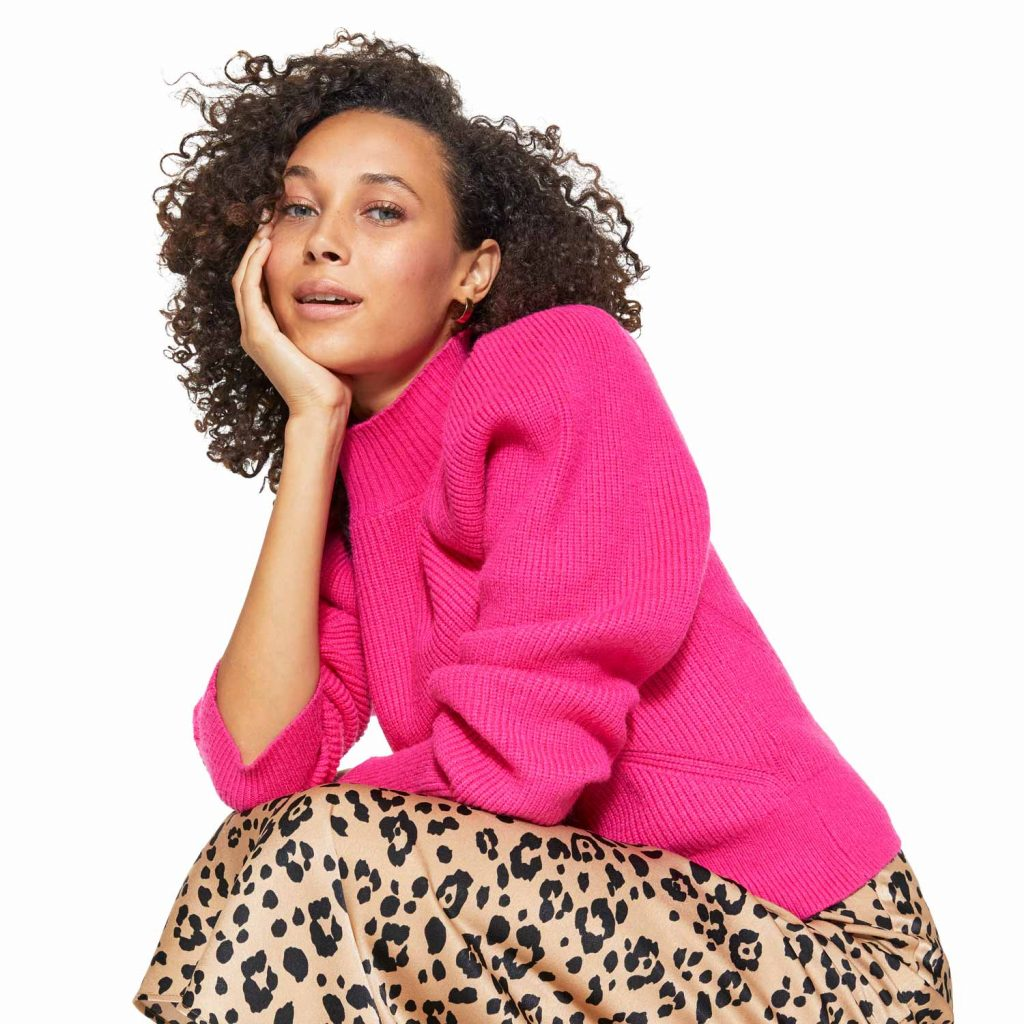 Image of Woman with Curly Hair in Pink Sweater with Animal Print Skirt